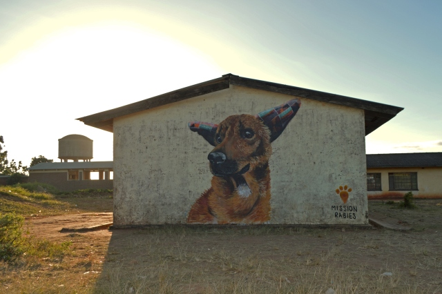 Dog mural on the side of a brick building