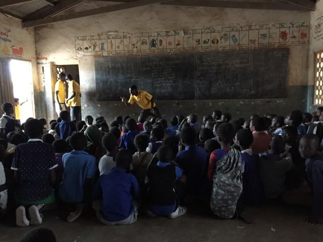 Schoolchildren sit on a classroom floor as a man in a Mission Rabies t-shirt speaks