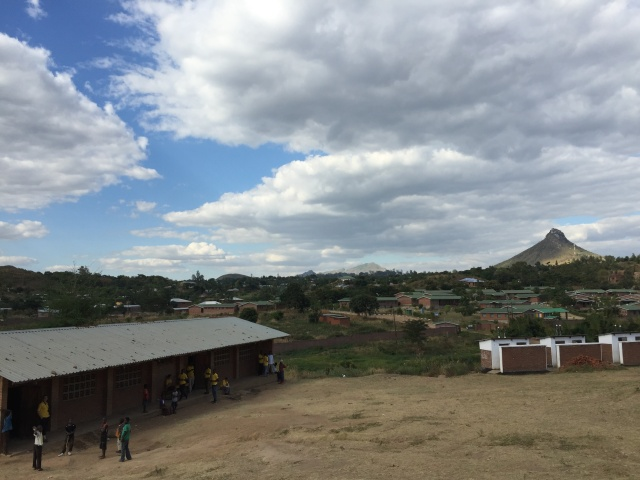 People outside a building with a village, trees and a mountain in the background