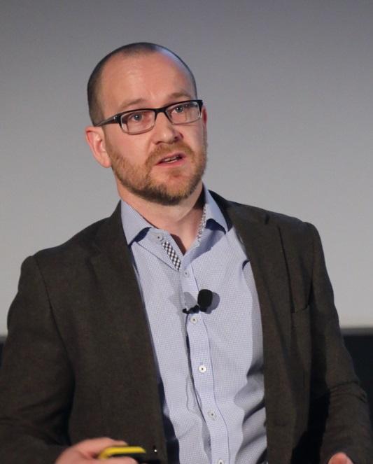 A man mid speech, wearing a microphone