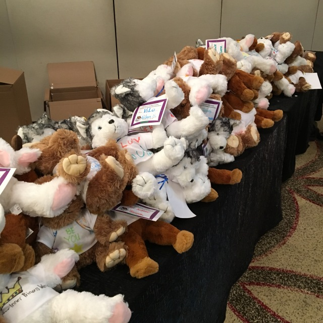Various teddy bears are piled up on a long table, with open boxes on the floor behind
