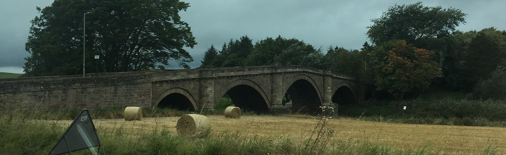 Landscape view of hay bales in a field with an old stone bridge and trees in the distance