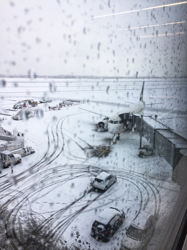 A view from a wet window showing a plane and vehicles on a snowy airport apron