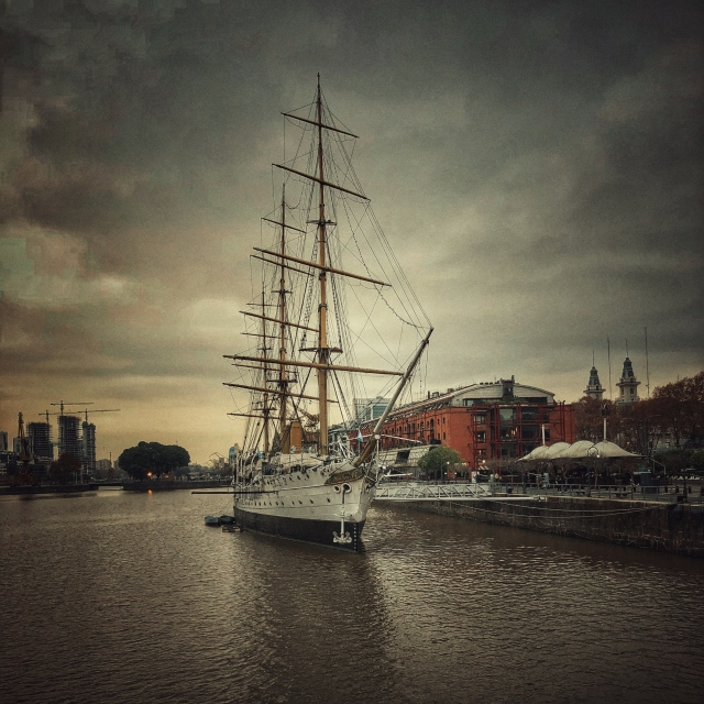 Tall Sailing Ship docked at a quayside, with city buildings in the background
