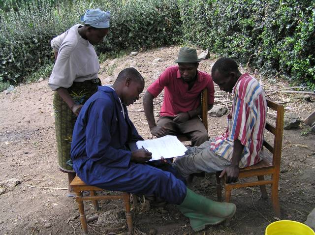 Herdsmen sitting in a group on chairs outside, writing up notes from sampling