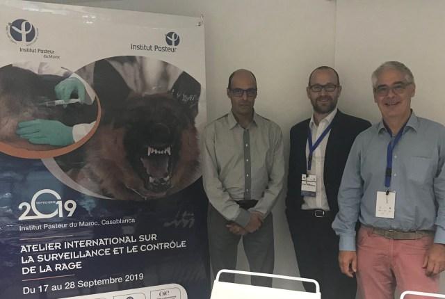 3 delegates standing beside a workshop poster