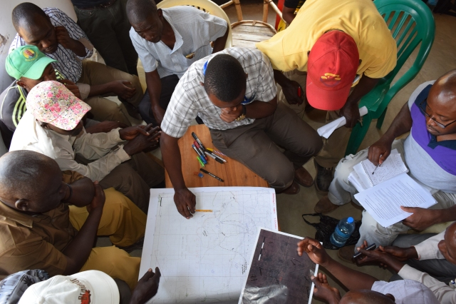 Focus On Tracking the movement of livestock - Group of men sat around a table studying a map