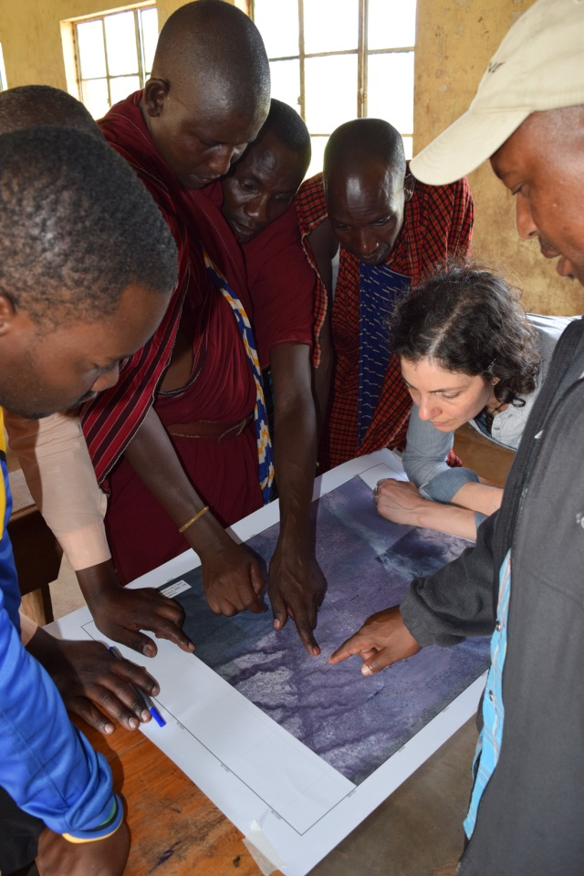 Focus On Tracking the movement of livestock - group of people studying a map